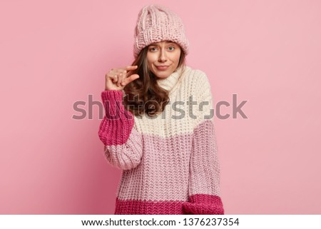Close up shot of beautiful lady forms something tiny, makes hand gesture, has displeased facial expression, wears fashionable winter clothes, poses against pink background. Very little or small #1376237354