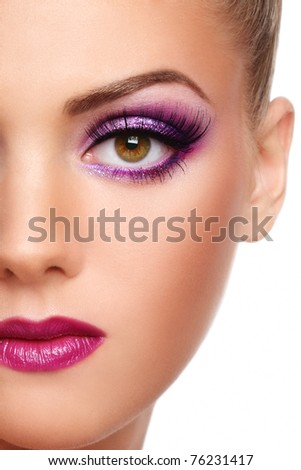 Close-up shot of beautiful woman face with stylish violet make-up