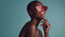 Close up shot of beautiful woman in sunglasses and red lips against grey background. African female model with funky sunglasses.