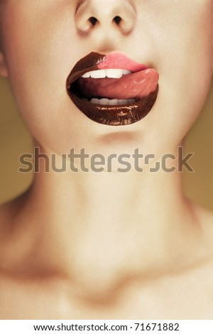 Close-up shot of beautiful woman lips with chocolate, girl licking her lips. Conceptual image.