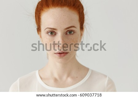 Close up shot of beautiful young redhead European female with extraordinary appearance relaxing indoors. Good-looking pretty girl with ginger hair and freckles all over her face posing at white wall - Shutterstock ID 609037718