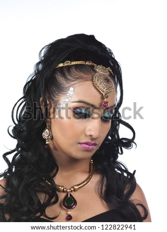 Close-up shot of beautiful young woman wearing make-up and jewelry over white background