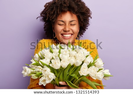 Close up shot of black ethnic young woman with crisp hair, smiles broadly, feels pleased, gets flowers from beloved person, models over purple background. Spring holiday and Womens Day concept