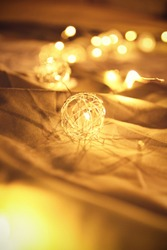 Close up shot of blurred golden Christmas lights on rumpled bed sheets, making cozy and romantic atmosphere. Festive bukeh background with lights.