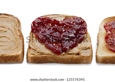 Close-up shot of bread toast with peanut butter spread and jam.