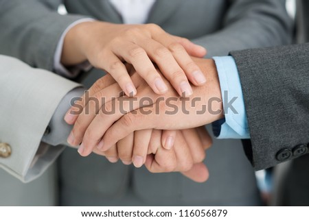 Close-up shot of business people putting their hands together to give support to a new project