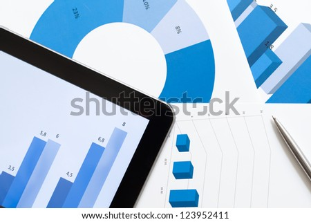 Close up shot of business stationery: tablet and documents with diagrams - stock photo