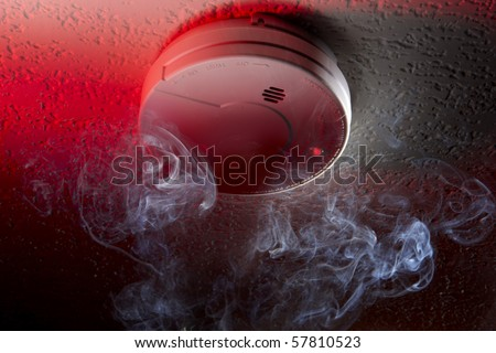 Close up shot of ceiling mounted smoke detector with white smoke and red warning light