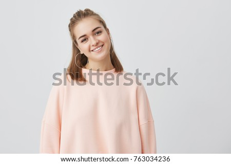 Close up shot of charming Caucasian female with fair straight hair dressed in pink, gently looking at camera, smiling while listening to interesting stories and good news. Tender, beautiful, young.