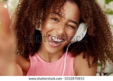 Close up shot of cheerful African American female listens pleasant music with headphones, poses for selfie, being in good mood. Teenage dark skinned girl enteratins herself with modern device #1032870853