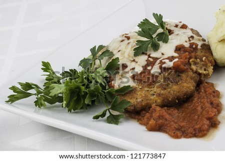 Close up shot of chicken parmesan with parsley garnish