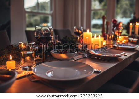 Close up shot of christmas festive table with no people. Dining table with plates, wine glasses and candles. #725253223