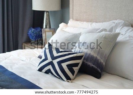 Close up shot of comfortable blue pattern cushions and white pillows on the white bed