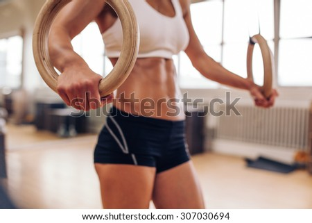 Close up shot of crossfit female athlete holding gymnastic rings. Mid section shot of woman exercising with rings at gym.