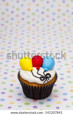 Close-up shot of cupcake with multi colored balloons  over polka dots background.