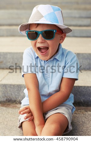 90e88a0b0705 Close-up shot of cute small boy in sunglasses and hat sitting on stairs with