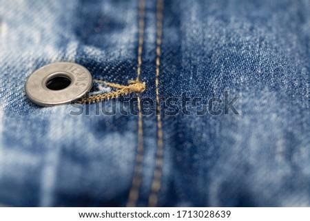 Close-up shot of denim jacket, denim stitch, denim jacket button, denim jacket's buttonhole