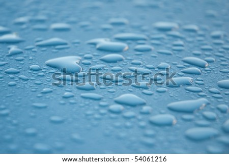 Close-up shot of dew drops on a light blue or turquoise metallic surface, glistening from the light