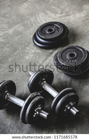 close-up shot of dumbbells with weight plates on concrete surface