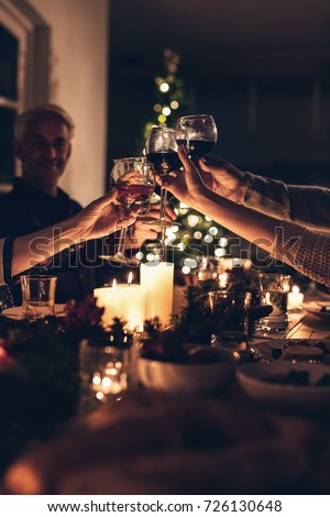 Close up shot of family toasting wine at christmas dinner. Family enjoying christmas dinner together at home, with focus on hands and wine glasses.