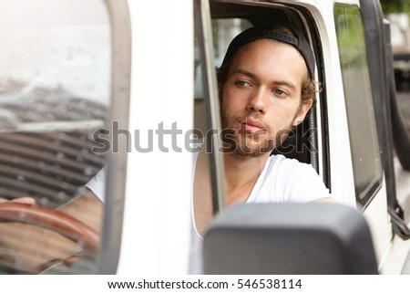 e2ae106a138 Close up shot of fashionable young unshaven man wearing cap backwards