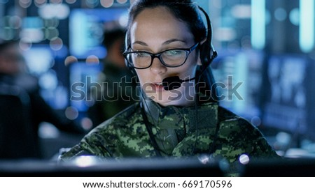 Close-up shot of Female Army Officer Using Computer in Headphones. In the Background Busy System Control Center with People Working, Displays with Information.