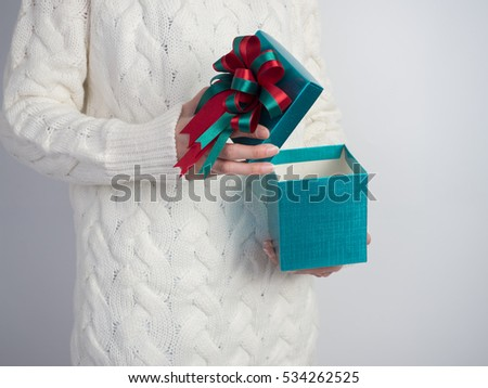 Close up shot of female hands holding and open gift box and nice ribbon. Gift box color in the hands of a woman wearing a knitted hat sweater on white background.