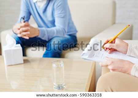 Close-up shot of female hands of psychologist making necessary notes in medical card with pencil during therapy session
