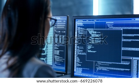 Close-up Shot of Female IT Engineer Working in Monitoring Room. She Works with Multiple Displays. #669226078