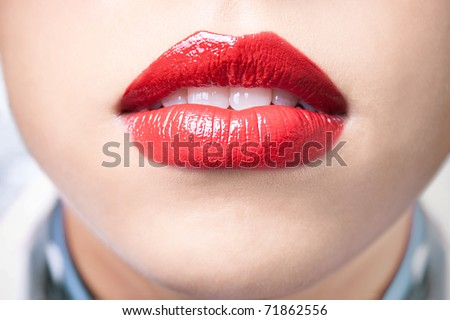 Close-up shot of female lips with bright red lipstick