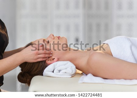 Close up shot of female young masseur hands making facial and temporal massage for female attractive client in massage studio. Side view.