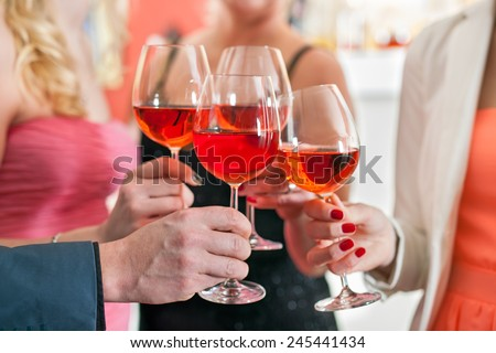 Close up Shot of Friends Tossing Glasses of Red Wine in a Party. #245441434