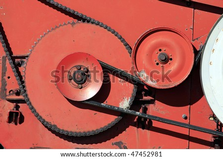 Close-up shot of gears and chains on a old piece of farming equipment.