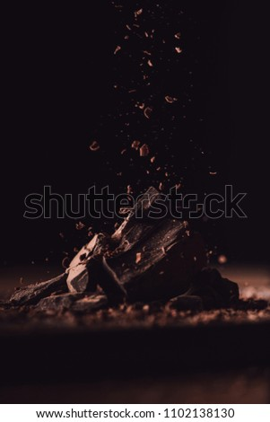 close up shot of grated dark chocolate falling on pieces of chocolate on black background