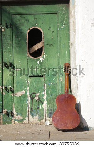 Close up shot of guitar and abandoned vintage door exterior