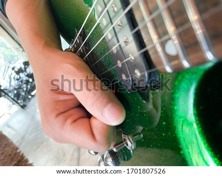 close up shot of guitarist hands playing sparkle green guitar with focus on hands stock photo