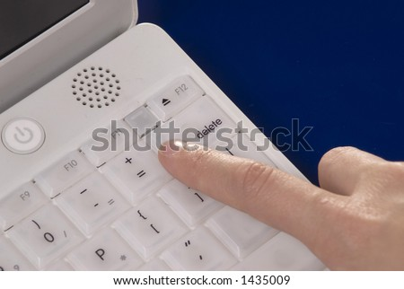 close up shot of hand and keyboard of a white laptop