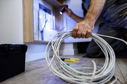 Close up shot of hand of aged electrician repairman in uniform working, fixing, installing ethernet cable in fuse box, holding flashlight and cable. Selective focus on hand and cable. Horizontal shot