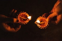 Close up shot of hands of two woman holding lit diya during Indian festival Diwali