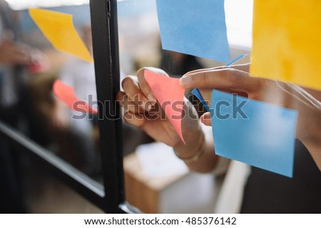 Close up shot of hands of woman sticking adhesive notes on glass wall in office