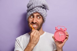 Close up shot of handsome male with stubble, wakes up in morning, holds alarm clock showing time, brushes teeth with toothpaste, wears white t shirt and towel on head, isolated over purple background