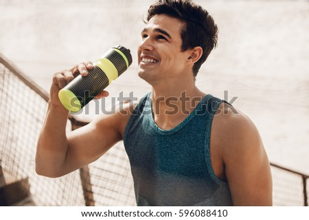 Close up shot of happy young man drinking water after workout outdoors. Fit male runner resting after training session and laughing. #596088410