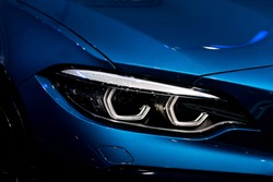 Close up shot of headlight in luxury  blue car background. Modern and expensive sport car concept