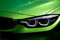 Close up shot of headlight in luxury  green car background. Modern and expensive sport car concept