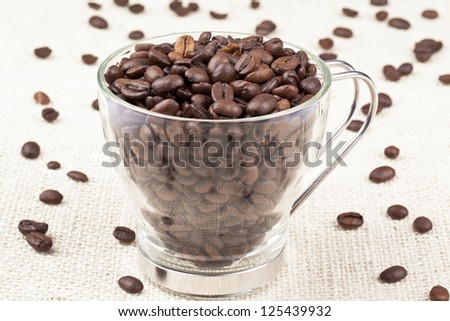 Close-up shot of heap of coffee beans in coffee mug.