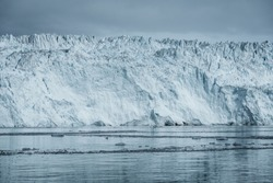 Close Up shot of huge Glacier wall. Large chunks of ice breaking off. Moody and overcast weather. Eqip Sermia Glacier called Eqi Glacier. Greenlandic ice cap melting because of global warming.