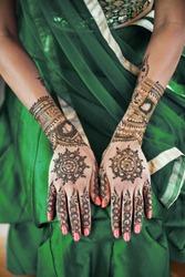 Close-up shot of Indian bride back hand with mehndi (henna tattoo) with beautiful sari in green lehenga