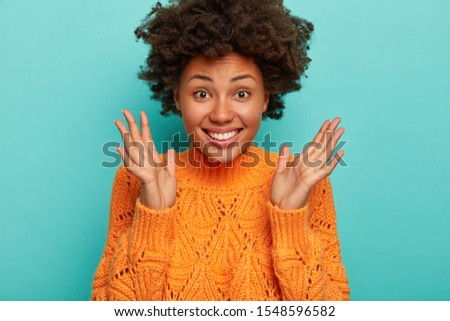 Close up shot of joyful curly woman expresses enthusiasm and joy, keeps palms raised, smiles broadly, wears bright winter sweater, enjoys amusing night with friends, isolated on blue background #1548596582