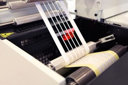 Close-up shot of labels manufacturing on flexo printing machine. Photo detail of matrix waste or trim removal from adhesive material on flexographic press.