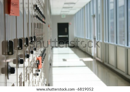 close-up shot of lockers in a row in hallway with exit door in center of shot
